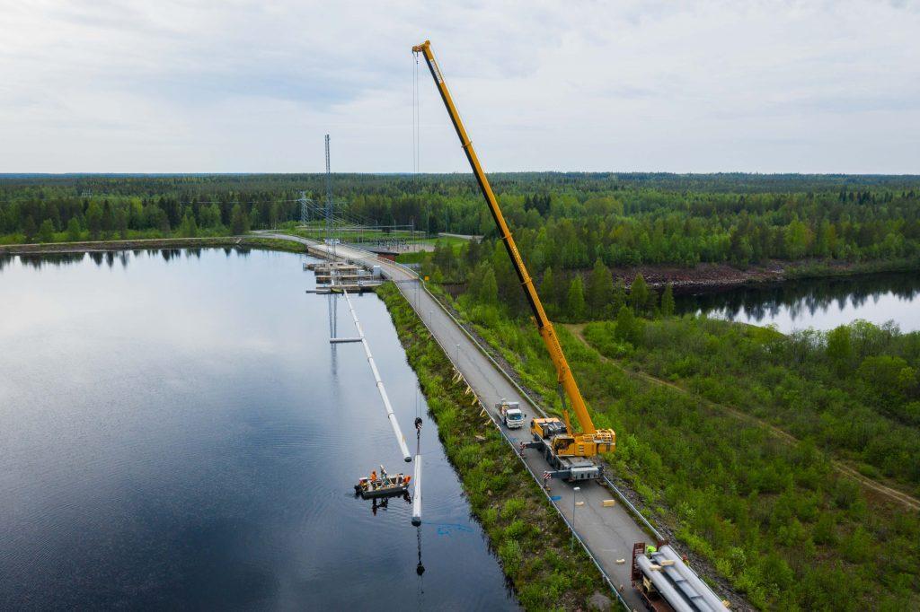 Nosturi nostaa ohjausaidan osia veteen voimalaitoksen yläkanavalla.