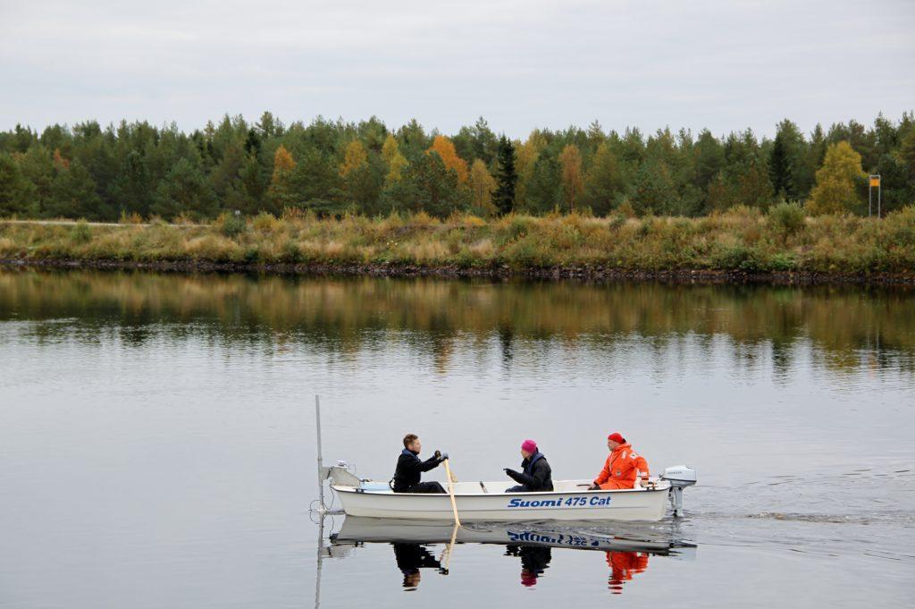 Syksyinen jokimaisema, veneessä kolme henkilöä tekemässä tutkimusta.