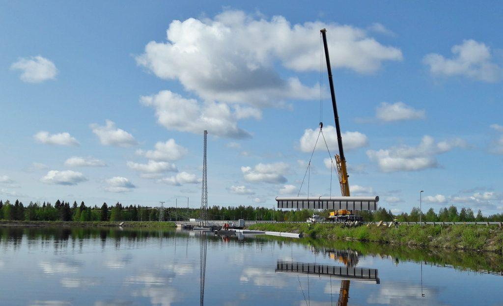 Nosturi nostaa ohjausaidan kahta yhteenliitettyä osaa veteen.